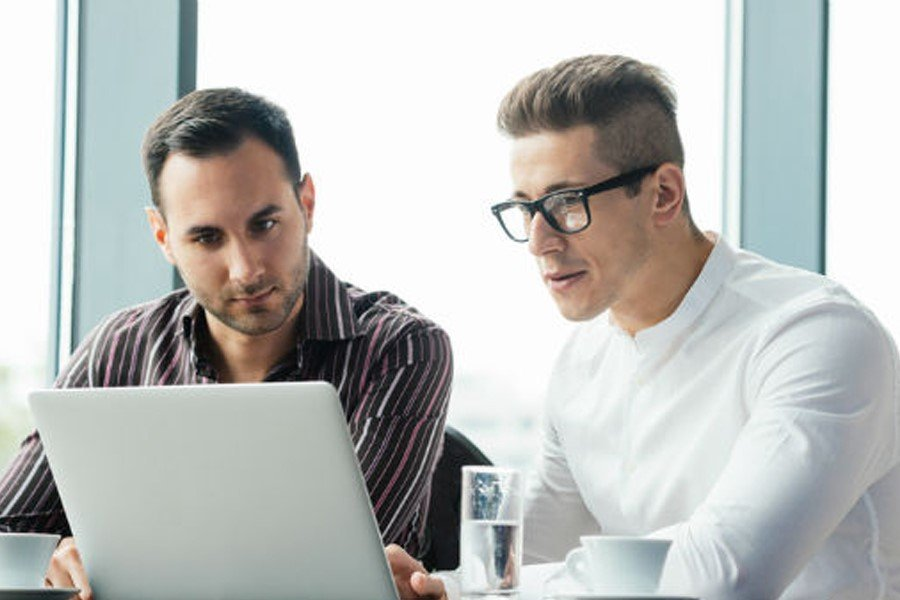 Two men looking at a laptop screen